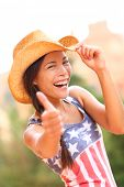 American cowgirl woman happy excited giving thumbs up wearing cowboy hat outdoors in countryside. Ch