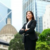 Businesswoman confident outside. Business woman standing proud and successful in suit cross-armed. Y
