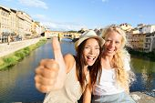 Happy women girl friends on travel in Florence. Cheerful girlfriends thumbs up smiling happy portrait outdoor by Ponte Vecchio during vacation holidays in Florence, Tuscany, Italy, Europe.