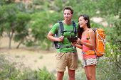 Tablet computer - couple hiking using internet and tablet computer pc guide book app on hike in Zion National Park. Interracial active hiker couple, Asian woman, caucasian man trekking in Utah, USA.