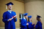 Friendly students in graduation gowns interacting, confident guy standing in front