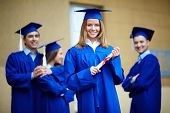 Friendly students in graduation gowns looking at camera with happy girl in front