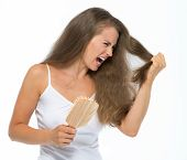 Stressed Young Woman Combing Hair