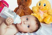 Baby with blue eyes drinking from a bottle