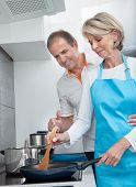 Happy Mature Couple Cooking Food In Kitchen