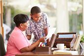 stock photo of grandmother  - Grandmother Showing Document To Grandson - JPG