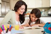 Mother Helping Daughter With Reading Homework At Table