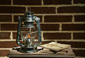 Burning kerosene lamp and letters on brick wall background