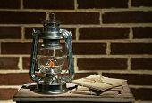 Burning kerosene lamp and letters on brick wall background