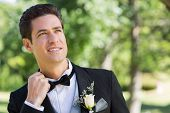 Nervous groom looking up in garden