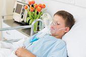stock photo of hospital gown  - Sick little boy wearing oxygen mask in hospital ward - JPG