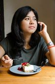 Young Woman Talking Mobile Phone With A Cake In Cafe