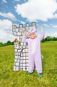Boy in costume of monster stands near drawn tower