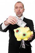 Businessman Shredding Dollars In A Piggy Bank