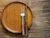 cutlery (knife and fork) on wooden plate
