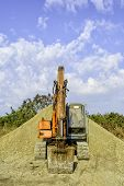 image of earth-mover  - Parked earth mover on top of gravel mound - JPG
