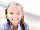 Portrait Of Adorable Smiling Little Girl In The Park