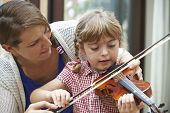Teacher Helping Young Female Pupil In Violin Lesson