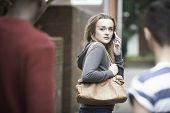Teenage Girl Using Phone As She Feels Intimidated On Walk Home