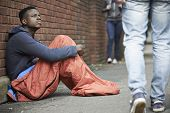 stock photo of beggar  - Homeless Teenage Boy In Sleeping Bag On The Street
