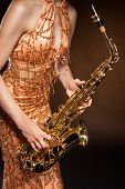 Young woman posing with saxophone at studio