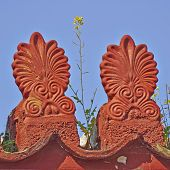 stock photo of neoclassical  - yellow flower on vintage neoclassical roof antefix - JPG