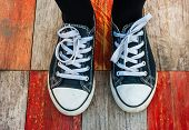 Sneakers on grunge wood deck background