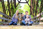 Family Of Four People And Dog Sitting On Bridge In Autumn