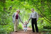 Young Grandparents Walking With Their Baby Granddaughter In A Park