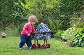 Adorable Curly Baby Girl Playing With A Vintage Toy Stroller In The Garden