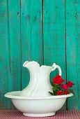 Antique water pitcher and basin with red flowers (roses) by rustic green background