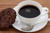 stock photo of chocolate-chip  - Chocolate chip cookie with a cup of black coffee in a white cup - JPG
