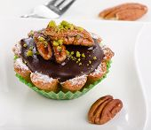 Chocolate Cupcake With Nuts On White Plate