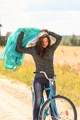 Beautiful brunette girl at cycling on dirt road