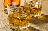 Two glasses of whisky and a bottle