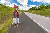 Woman walking beside road with traditional bag on her head