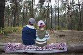 Children Sitting On A Log In The Autumn Forest And Waiting When The Fire Ready Meals.