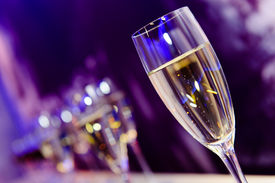 picture of champagne color  - Tall wine glass with white champagne lit by the festive lights on the dark - JPG