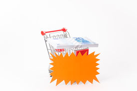 foto of caddy  - Caddy for shopping with money stack on white background - JPG