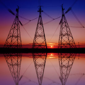 image of electricity pylon  - metal electricity pylon transmit electricity reflected in the water - JPG