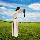 yelling young woman with small man over green field and blue sky