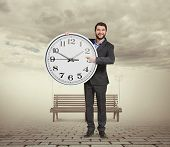 smiley businessman holding big clock, pointing at dial plate and looking at camera. photo at outdoor