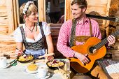 Couple on mountain hut eating Kaiserschmarrn, a traditional Austrian pancake