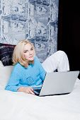 Young Girl Sitting On Bed With Laptop At Home