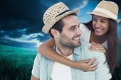 Happy casual man giving pretty girlfriend piggy back against blue sky over green field