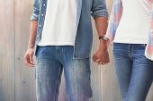 Hip young couple holding hands against pale grey wooden planks