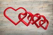 Linking hearts against bleached wooden planks background