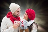 Winter couple holding mugs against black abstract light spot design