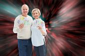 Happy mature couple smiling at camera showing money against digitally generated twinkling light design