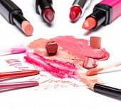image of  lips  - Different colors of smeared and sliced lipstick lip gloss with brushes lip liner on white textured surface - JPG